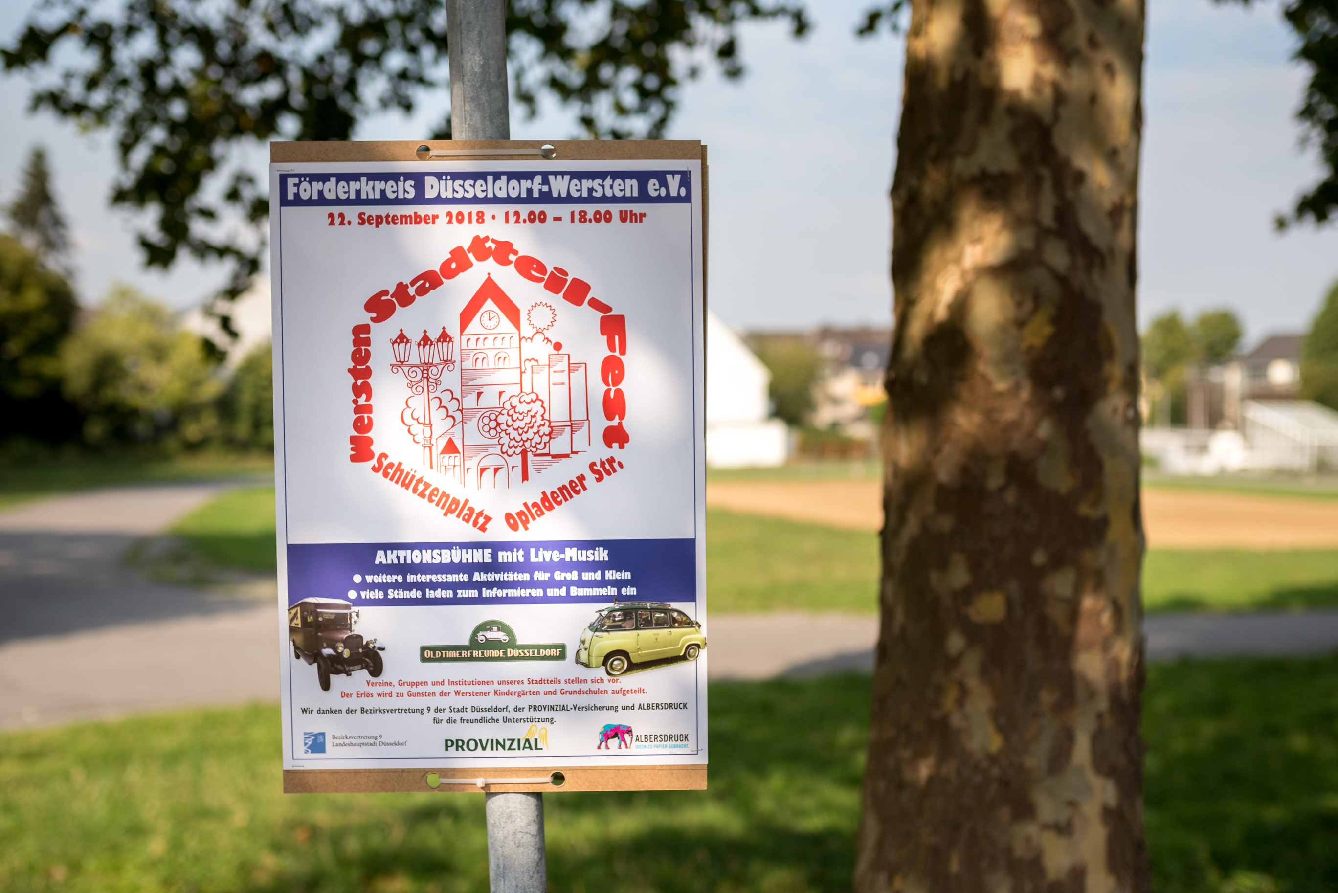 Ein Plakat hängt an einem Pfahl. Dort ist die Einladung zum Stadtteilfest zu erkennen. Im Hintergrund ist der (noch) leere Schützenplatz zu sehen.