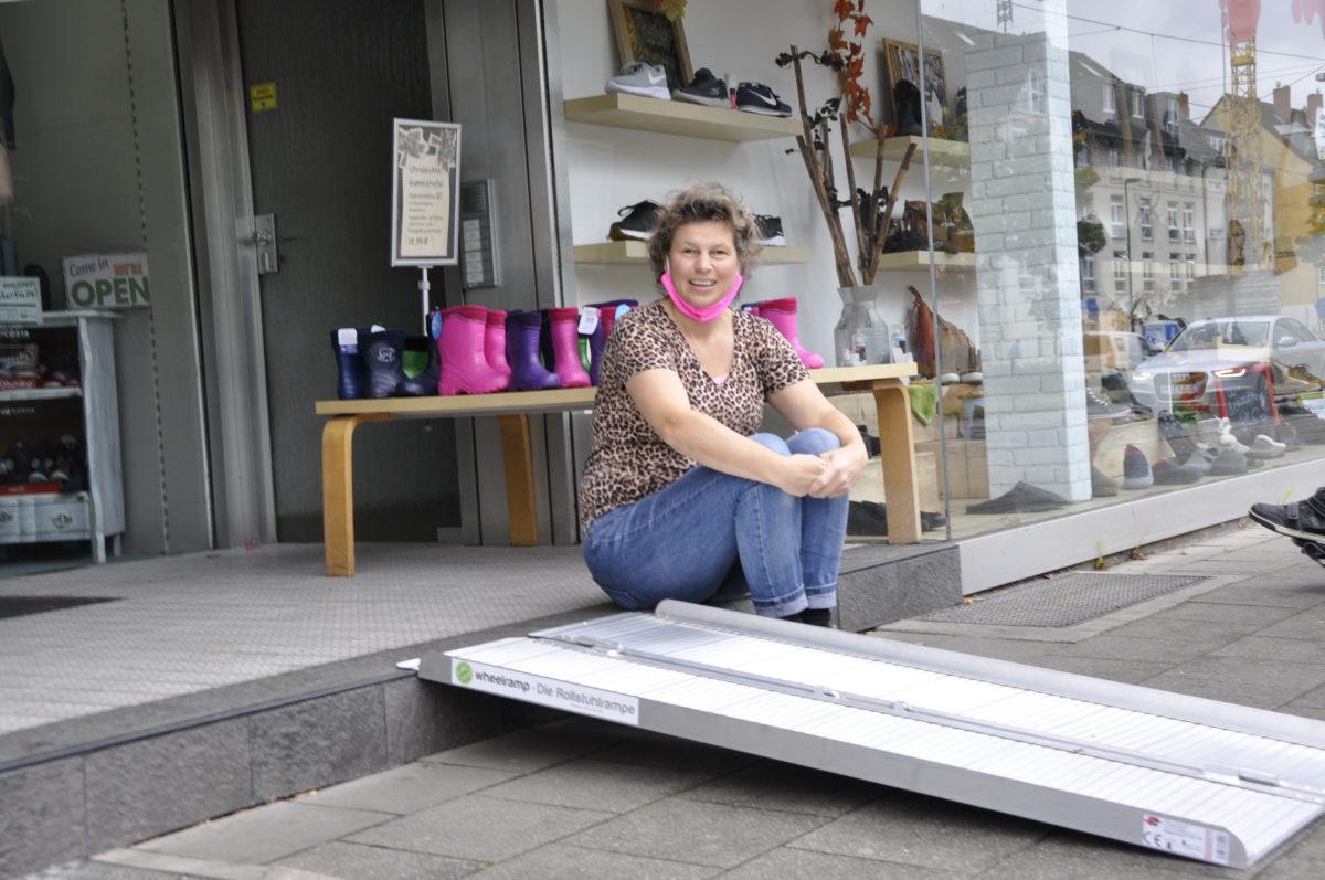 Auf dem Foto ist die mobile Rampe vor dem Eingang von Dengler Schuhe zu sehen. Diese liegt passgenau und fest auf der Stufe und ermöglicht so allen Rollstuhlfahrern einen barrierefreien Zutritt. Daneben sitzt die Inhaberin des Schuhgeschäfts.