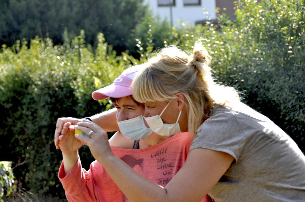 Zwei Damen halten eine Kamera fest, um ein Foto zu machen.